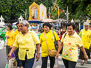 04 DECEMBER 2012 - BANGKOK, THAILAND: Women dressed in yellow cross a Bangkok street near a portrait of Bhumibol Adulyadej, the King of Thailand, Tuesday. Yellow is the official color of the Thai King, who celebrates his 85th birthday Wednesday, Dec. 5. He is expected to make a rare public appearance and address the nation from Mukkhadej balcony of the Ananta Samakhom Throne Hall in the Royal Plaza. The last time he did so was in 2006. His birthday is a public holiday in Thailand and hundreds of thousands of people are expected to jam the streets around the Royal Plaza and Grand Palace to participate in the festivities.    PHOTO BY JACK KURTZ