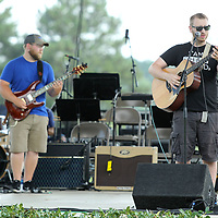 Michael Thomas, leading singer of Bonfire Orchestra from Tupelo, plays with the band on stage during the Pallard Park Picnic in the Park Wesnesday afternoon in Tupelo.