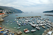 Elevated view of harbour with small pleasure craft in foreground and huge Cruise liners and replica sailing ship in background, Dubrovnik old town, Croatia