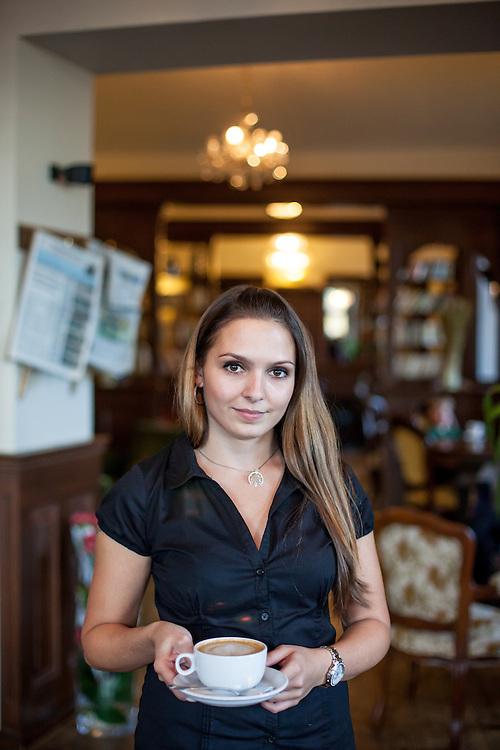 Angestellte des Cafe Bella Vida mit dem exzellenten Milchkaffee in den Räumlichkeiten des Cafes.