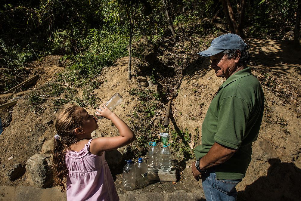CARACAS, VENEZUELA - JANUARY 23, 2016:  Jesus Pinto, 61, fills jugs of water trickling down from the Avila mountain with his six-year-old granddaughter, Zahir Pinto.  Caracas has the look of a modern city, filled with fast cars and high skyscrapers. But its infrastructure is crumbling. A drought, the product of this year's El Niño, means water shortages.  Here at a point under the Ávila mountain overlooking the city center, the water is free: It trickles right out of the mountain and onto the pavement. So starting early in the morning, hundreds of people pull over and wait their turn. Their bottles hold their place in line.  PHOTO: Meridith Kohut for The New York Times