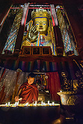 China, Tibet, Shigatse, Thashilumpo Monastery, Seated Maitreya Buddha monk tending butter lamps