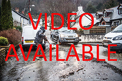 VIDEO AVAILABLE  https://www.dropbox.com/sh/r9bgvbg9esyb4sw/AAB_SZkNIWyuif2TS2KvSEmAa?dl=0  © Licensed to London News Pictures. 21/01/2018. Llandre,  UK. Flood water cascades like a river down the main street in LLANDRE near Aberystwyth in Mid Wales, after hours of torrential rain caused the small steam that runs through he village to dramatically burst its banks . Local residents  made improvised sandbags and barriers to try to divert the water away from their houses. The stream overflowed high above the village just outside the parish church, sending debris down and washing away parts of the road surface .Photo credit: Keith Morris/LNP