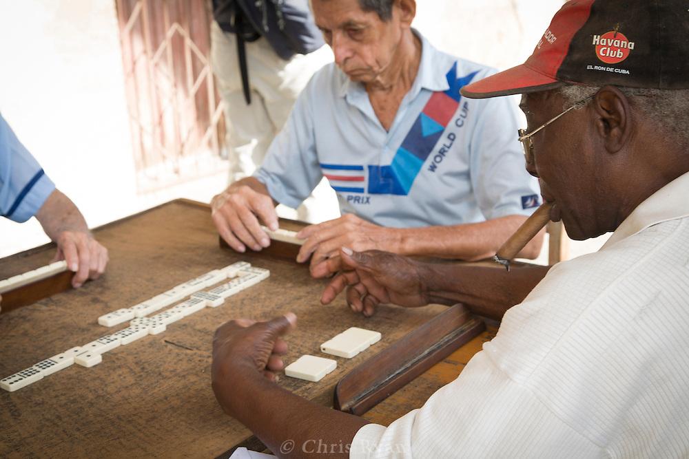 Elderly men playing dominos on a sidewalk, Havana, Cuba