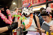 UNITED KINGDOM, London: 24 May 2019 <br /> A cosplay fan dressed as a Star Wars Supertrooper drinks a cocktail in the ExCeL Centre in London for the MCM London Comic Con. Thousands of cosplay enthusiasts will come to the ExCeL Centre across the next three days to enjoy the convention.