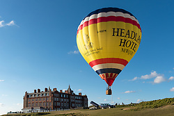 A colourful hot air balloon takes to the sky above the Headland Hotel in Newquay, Cornwall.