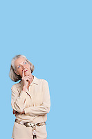 Contemplative senior woman in casuals with hand on chin against blue background