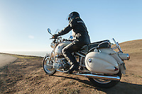 Rider in black leather sitting on a 1960s BMW R60US motorcycle (PR) on the side of a coastal road in Sonoma County California.