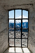 "Window to a wild rocky alpine landscape. Ascend to Skålatårnet (""Skåla tower"" or Kloumanntårnet, 1843 meters / 6047 feet elevation) on Skåla, the highest tidewater mountain in Norway.  Doctor Kloumann built the tower in 1891 with hopes to cure clients with tuberculosis. The hike starts east of Loen village in Stryn municipality, Sogn og Fjordane county, Norway. Between Tjugen camping and Loenvatnet, park at the pay lot and ascend steeply on a well marked trail. Stepping stones greatly improve footing on the upper portion protected within Jostedalsbreen National Park (nasjonalpark). Hikers allow at least 5 hours up and 3 hours down on this strenuous ascent of 1800 meters (6000 feet). For a fee, the public can sleep in the tower's 22 beds, as administered by Bergen Turlag, a subsidiary of the Norwegian Trekking Association (DNT)."