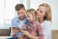 Parents with daughter using digital tablet at home
