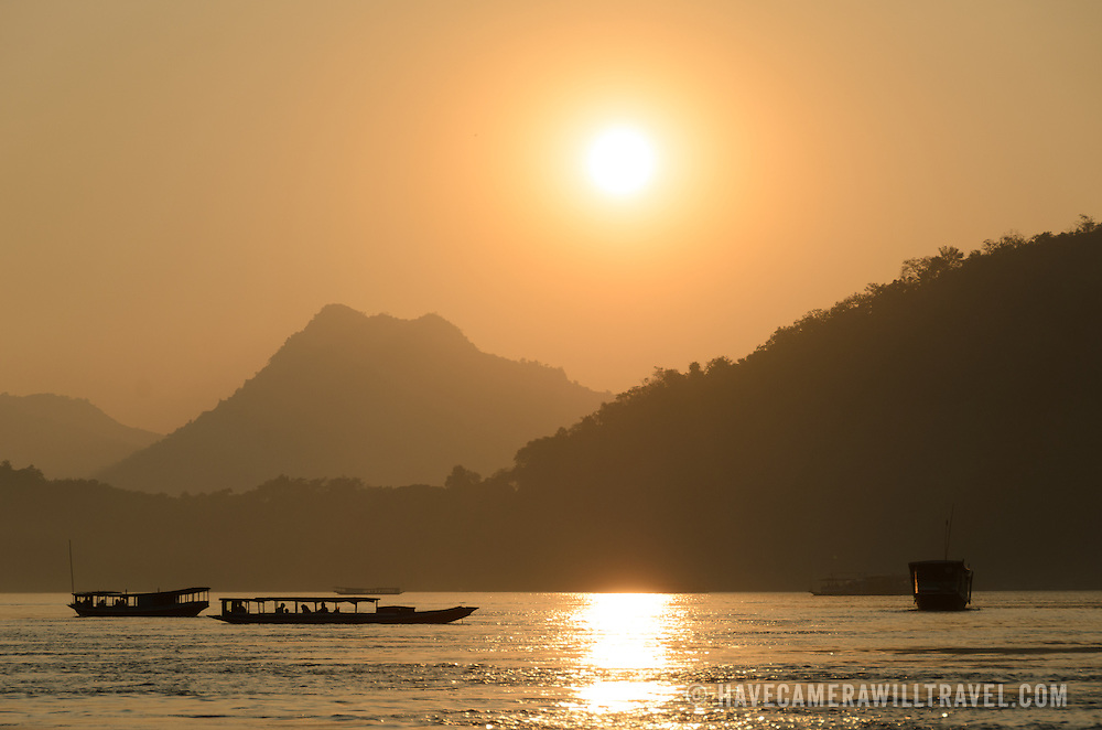 Boats crossing the river at sunset on the Mekong River near Luang Prabang, Laos.