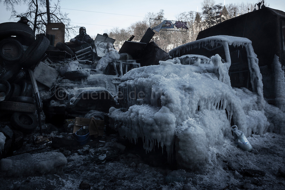 Perched on charred police trucks caked with ice, an anti government protester stands guard on Hrushevskoho street barricades near Maidan Square during standoff with riot police while a truce was agreed, in Kiev, 27 January 2014.