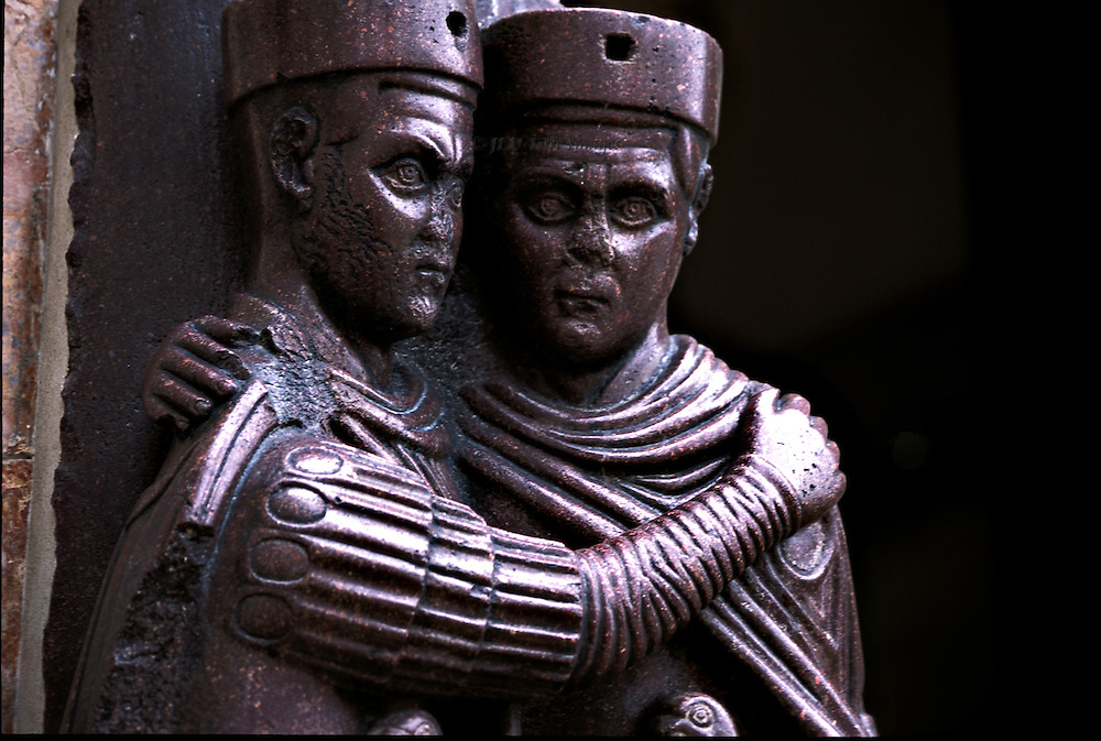 The Tetrarchs, porphyry sculptures on wall of San Marco, Venice. Close up of two heads and arms, the facial expression of each a blank stare.  Their posture of an embrace was meant to convey that the four emperors would work as one.   The sculpture was taken from Constantinople during the 4th Crusade, in 1204, and installed on the southwest corner of the cathedral..