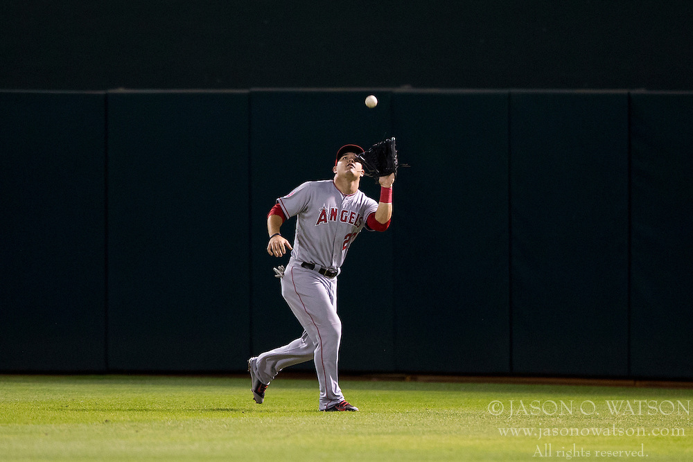 OAKLAND, CA - SEPTEMBER 23:  Mike Trout #27 of the Los Angeles Angels of Anaheim catches a fly ball against the Oakland Athletics during the seventh inning at O.co Coliseum on September 23, 2014 in Oakland, California. The Los Angeles Angels of Anaheim defeated the Oakland Athletics 2-0.  (Photo by Jason O. Watson/Getty Images) *** Local Caption *** Mike Trout