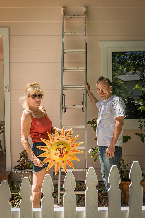 """Growing up in the north of Norway, I always dreamed of living in a sunny spot...I found it here in Calistoga.  This sun showed up in my clay and promised me a sunny future.""   -Torlid Roberts with her partner, Ernest Rankin, prepare to hang her ceramic sun on the front their home on Washington Street in Calistoga."