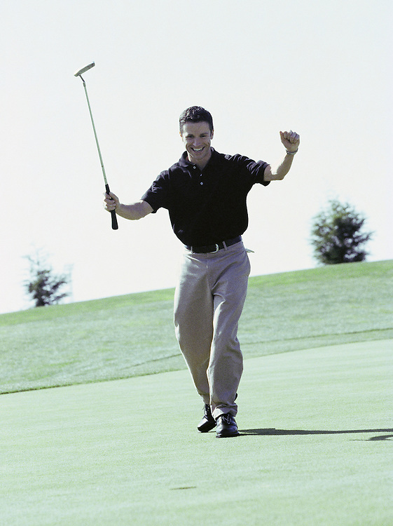 A young man celebrating on a golf green<br />