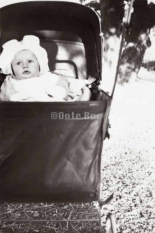 3 month old baby placed outside in the sun laying in a walking carriage