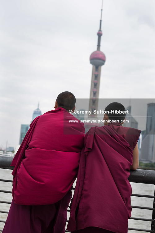 Two Buddhist monks looking out over Huangpu River, towards the Oriental Pearl TV Tower in Pudong, in Shanghai, China, Wednesday 6th June 2012.