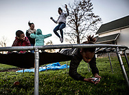 Daelesha Haile sneaks her head through a hole in the trampoline in her backyard while her sisters Daejahnae and Diamond, brother Dayvon and friend Samantha Elliot all jump around.The Haile children recently moved to Newark, Ohio from Detroit Michigan because their father believed there would be more opportunity and a quieter, safer life for them.