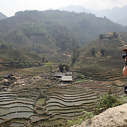 A western tourist takes pictures of terraced fields surrounding the village of Lao chai in the Highlands near Sapa, Northern Vietnam. The highlands are close to the Chinese border, inhabited by highland minorities including Hmong and Dzao groups. Sapa is now a thriving tourist destination for travelers taking the night train from Hanoi. Sapa, Vietnam. 16th March 2012. Photo Tim Clayton