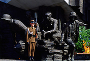 Soldier stands at attention with a rifle to guard the Warsaw Uprising Monument in Poland.