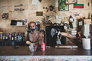 The owner of the Elvis Bar serves a Coke with ice to his first customer of the day, a passing photographer-pilgrim, in the small town of Reliegos, Spain. The Elvis Bar is a somewhat famous stopping point for many pilgrims on the Camino. (June 21, 2018)<br /> <br /> DAY 25: EL BURGO RANERO TO MANSILLA DE LAS MULAS -- 19 KM