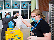 22 APRIL 2020 - DES MOINES, IOWA: KALY WOLFE (right) and FADYA HAROUN pack milk into grab and go meals at Edmunds Elementary School. Schools in Iowa are closed for the rest of the school year because of the COVID-19 (Coronavirus/SAR-CoV-2) pandemic. Des Moines Public Schools expanded their school lunch and distance learning efforts this week. Lunches are being distributed at all of the district's elementary and middle schools and officials have started distributing computers so students can participate in distance learning. The meal distribution was done according to social distancing guidelines.           PHOTO BY JACK KURTZ