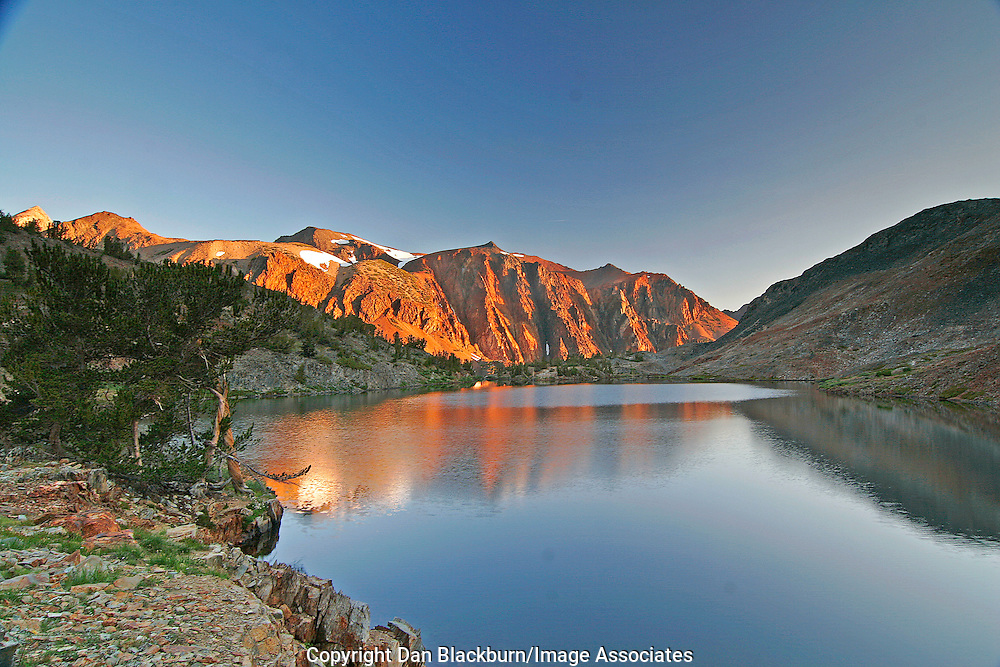 Sunrise lights up Shepherds Crest and reflections in Odell Lake in the Hoover Wilderness of the Sierra in California.