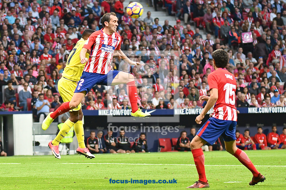 Diego God&iacute;n of Atletico Madrid heads clear under pressure from C&eacute;dric Bakambu of Villareal during the La Liga match at the Wanda Metropolitano Stadium, Madrid<br /> Picture by Kristian Kane/Focus Images Ltd +44 7814 482222<br /> 28/10/2017