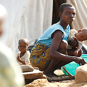 A woman holds her child while cooking outside the tent where they live after their home was destroyed by floods in the village of Kpoto, Benin on Wednesday October 27, 2010.