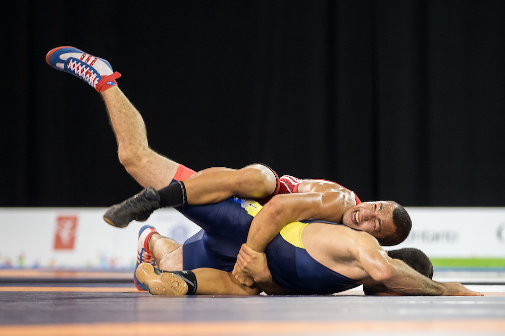 Maximiliano Prudenzano (top) of Argentina tries to roll Carlos Munoz of Colombia during their bronze medal bout  in the 75kg class of the men's greco-roman wrestling at the 2015 Pan American Games in Toronto, Canada, July 15,  2015.  AFP PHOTO/GEOFF ROBINS