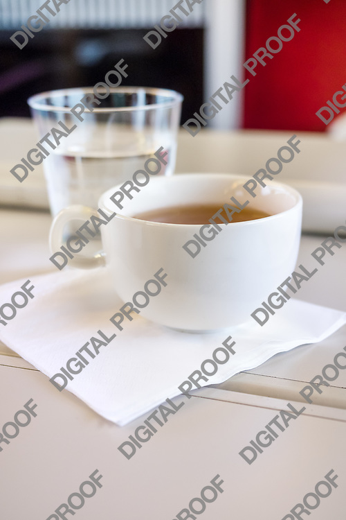 Tea cup with water over a white travel table