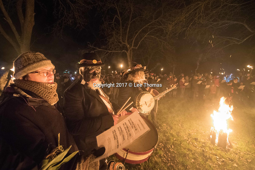Much Marcle, Herefordshire, UK. 6th January 2018. Pictured: People sing traditional wassail songs around the cider tree. / Hundreds of people both young and old gathered at the Westons Cider Mill and adjoining orchard to take part in the traditional Wassail ceremony. The event at Much Marcle in Herefordshire was attended by the Silurian morris side who entertained the crowd with witty repartee, raucous dancing and music. According to their website, the true origins of blackened faces are lost to history, but are widely believed to be simply a form of disguise, possibly to overcome the oppressive anti-begging laws of the 17th century, and the eternal embarrassment of being a morris man. The orchard-visiting wassail refers to the ancient custom of visiting orchards in cider-producing regions of England, reciting incantations and singing to the trees to promote a good harvest for the coming year. // Lee Thomas, Tel. 07784142973. Email: leepthomas@gmail.com  www.leept.co.uk (0000635435)