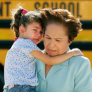McAllen, TX / 2006 - Thigpen Elementary School principal Elva de Leon carries pre-kindergarten student Joycelynn Martinez away from the scene of a bus accident in McAllen. The accident involved a McAllen Independent School District (ISD) school bus carrying six children and another automobile at Bentsen Rd. and Expressway 83. Officials at the scene said the driver of the automobile rear-ended the bus and was transported to McAllen Medical Hospital for treatment of injuries. No injuries to children were reported. Photo By Mike Roy / The Monitor