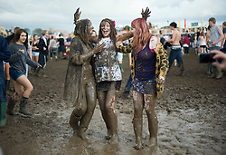 © Licensed to London News Pictures. 26/08/2011. Reading, UK. L to R Katherine Vincent (18), Jo Bligh (18) and Rosie Wallace (18) enjoying the mud on day one of Reading Festival 2011 in Reading, Berkshire today (26/08/2011). Photo credit: Ben Cawthra/LNP