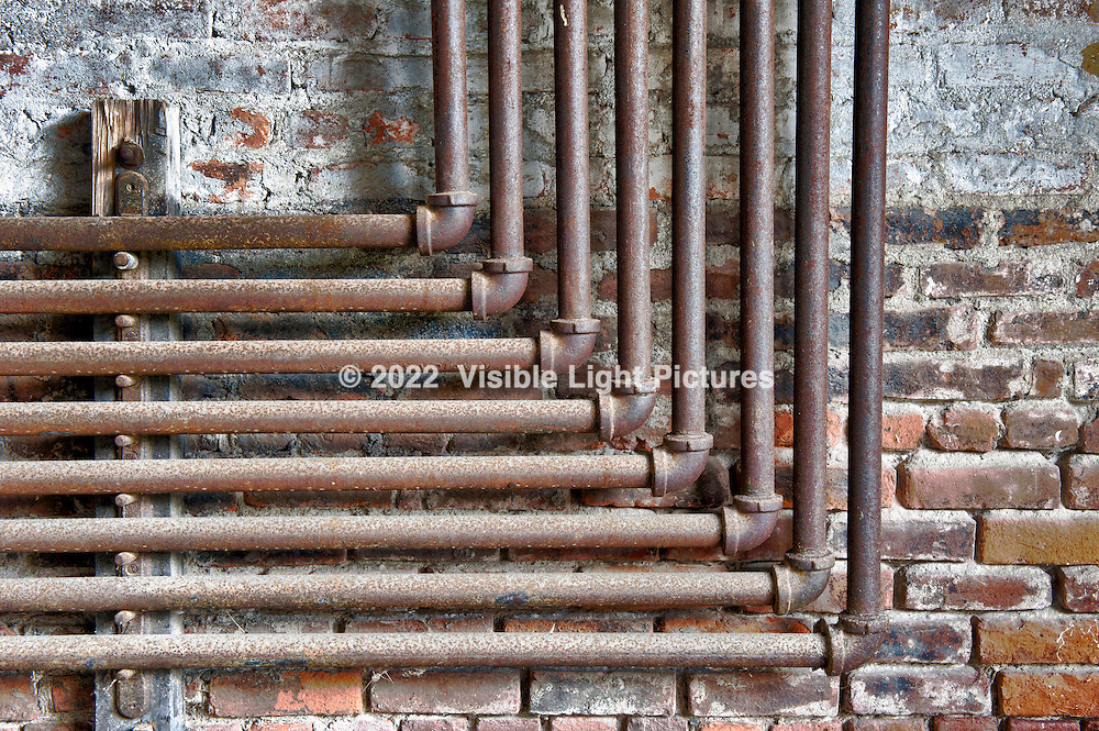 Stack of Heating Pipes against a Brick Wall.