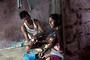 Mayuri Mahesh Pandit, 13, (right) is peeling potatoes inside her house, before leaving to participate at the Unicef-run 'Deepshikha Prerika' project inside the Milind Nagar Pipeline Area, an urban slum on the outskirts of Mumbai, Maharashtra, India, where she resides with her family. Her father, Mahesh Kashinath Pandit, 42, (left) is helping her with the food preparation.