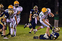 Lakeland High's Brendon Kedish bowls over Devin Smith from Timberlake after breaking through the line during the first half.