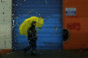 A pedestrian walks through the Chinatown-International District during rainstorms in Seattle. <br />