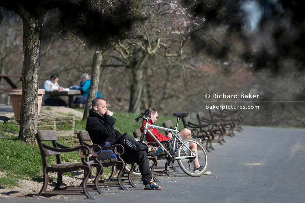 As the UK government considers further restrictions of movement in public places during the Coronavirus pandemic, a few south Londoners sit apart on benches in spring sunshine in Brockwell Park, Herne Hill, on 23rd March 2020, in London, England.