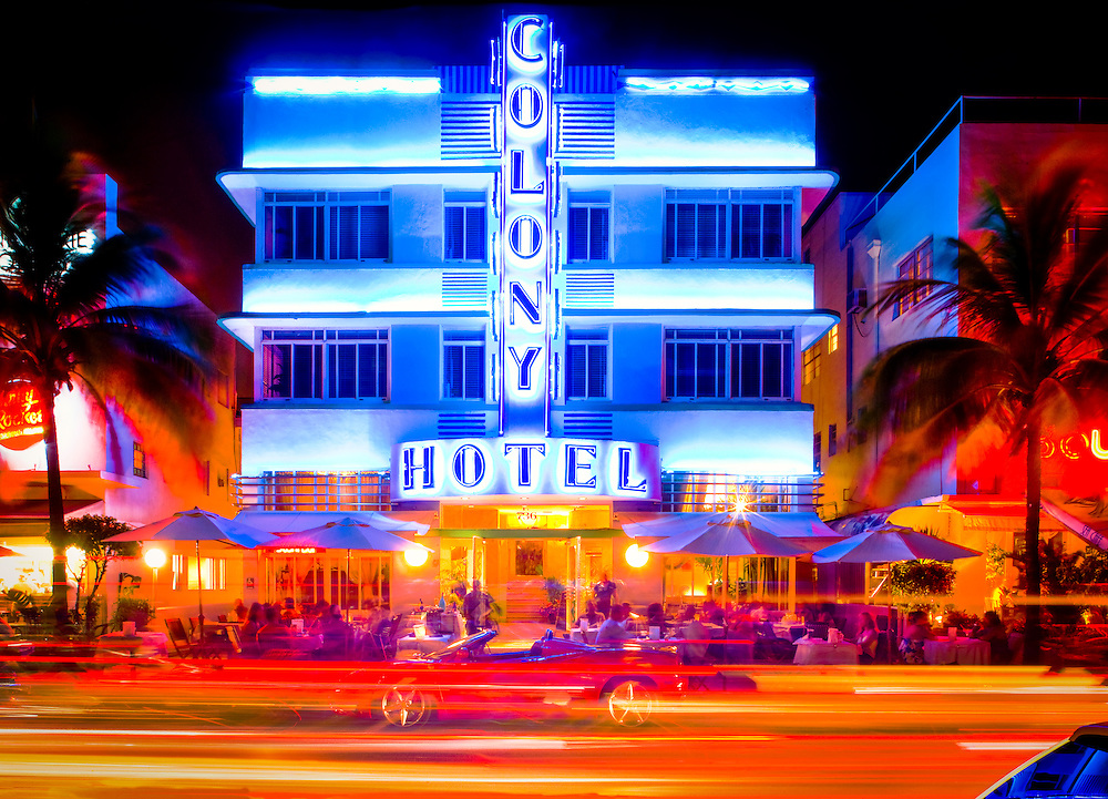 The neon-lit, Art Deco-style Colony Hotel and sidewalk cafe at night on Miami Beach's Ocean Drive in South Beach, with a  red Ferrari parked in front.
