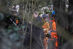 Harefield, UK. 8 February, 2020. Environmental activists from Extinction Rebellion hug trees in order to prevent HS2 engineers from using a chainsaw to carry out tree felling works for the high-speed rail project. The activists were successful in preventing any of the scheduled tree felling by HS2 and after an intervention by a police officer all tree felling and strimming work has now been cancelled for the weekend.