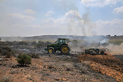 Farmer ploughs a burning field to contain the fire. This fire was caused by Palestinian Kite bombs that were flown from Gaza with a lit petrol soaked cloth, to set fires to Israeli fields and crops. Photographed on July 13, 2018 on the Israel Palestine (Gaza) Border
