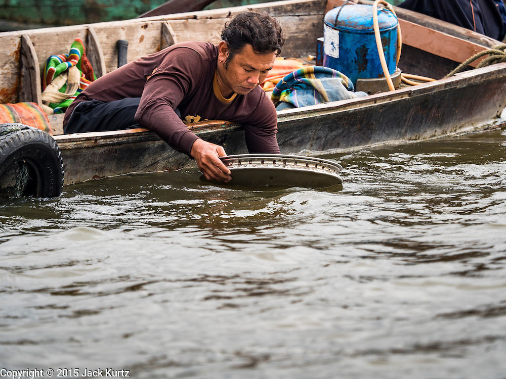 06 OCTOBER 2015 - BANGKOK, THAILAND:  A diver on a salvage diver's boat rinses off a pan full of scrap metal he brought up from the bottom of the Chao Phraya River in Bangkok. Divers work in two man teams on small boats in the Chao Phraya River. One person stays in the boat while the diver scours the river bottom for anything that can be salvaged and resold. The divers usually work close to shore because the center of the river is a busy commercial waterway with passenger boats and commercial freight barges passing up and down the river all day long. The Chao Phraya is a dangerous river to dive in. It's deep, has large tidal fluctuations, is fast flowing and badly polluted. The divers make money only when they sell something.    PHOTO BY JACK KURTZ