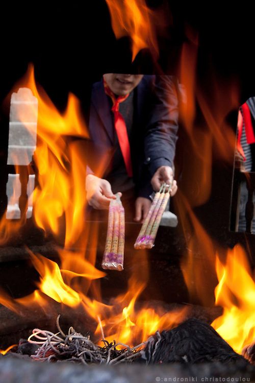 Asia, China, Hubei province.  Lighting incense sticks at Nanyan Temple on Wudang Moutain (Wudang-san), a World Heritage mountain with many Taoist monasteries.
