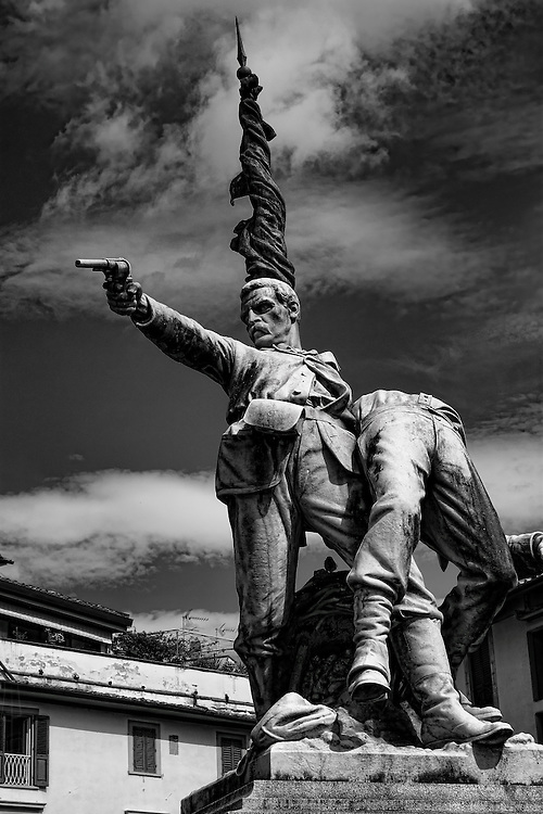 """A monument dedicated to 150 of Garibaldi's freedom fighters in Piazza Mentana, in Florence, Italy. The inscription in English reads: """"To the Brave who fell at Mentana, consecrating Rome to Free Italy."""""""