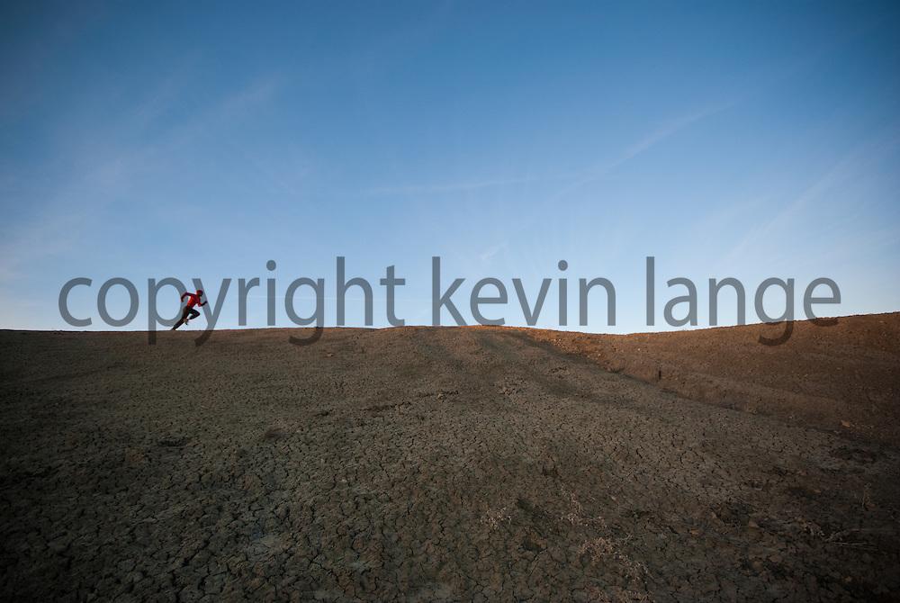 trail runner abstract desert landscape sky.  ojito wilderness, white mesa, new mexico.