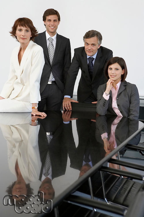 Four business colleagues at conference table portrait