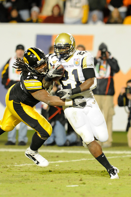 January 5, 2010: Running back Jonathan Dwyer of the Georgia Tech Yellow Jackets tries to elude defensive lineman Adrian Clayborn of the Iowa Hawkeyes during the NCAA football game between the Georgia Tech Yellow Jackets and the Iowa Hawkeyes in the Orange Bowl at LandShark Stadium in Miami Gardens, Florida. The Hawkeyes defeated the Yellow Jackets 24-14.