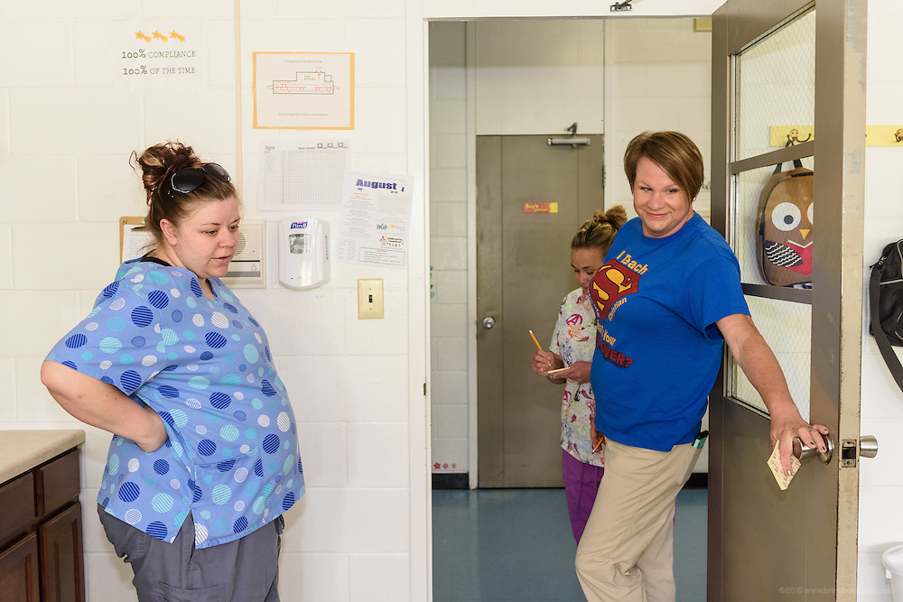 Jessica Lonyo, left a teacher at Southside Christian Child Care Day Care Center at 10315 Deering Road in Valley Station, talks with the director of the facility, Kristen Tipton, as she and Sabrina Nelson, food service manager, do their morning count. (Photo by Brian Bohannon)